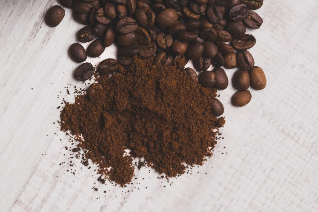 Coffee grounds beside ungrinded coffee beans