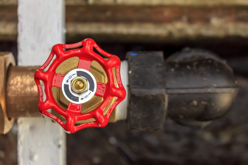 Close up of a red main water shut off valve for a home