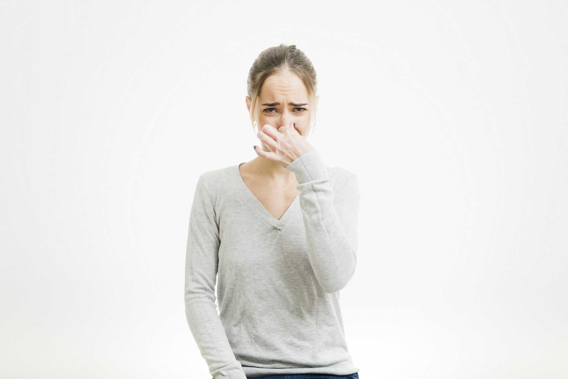 Woman plugging her nose because of bad sewer smell