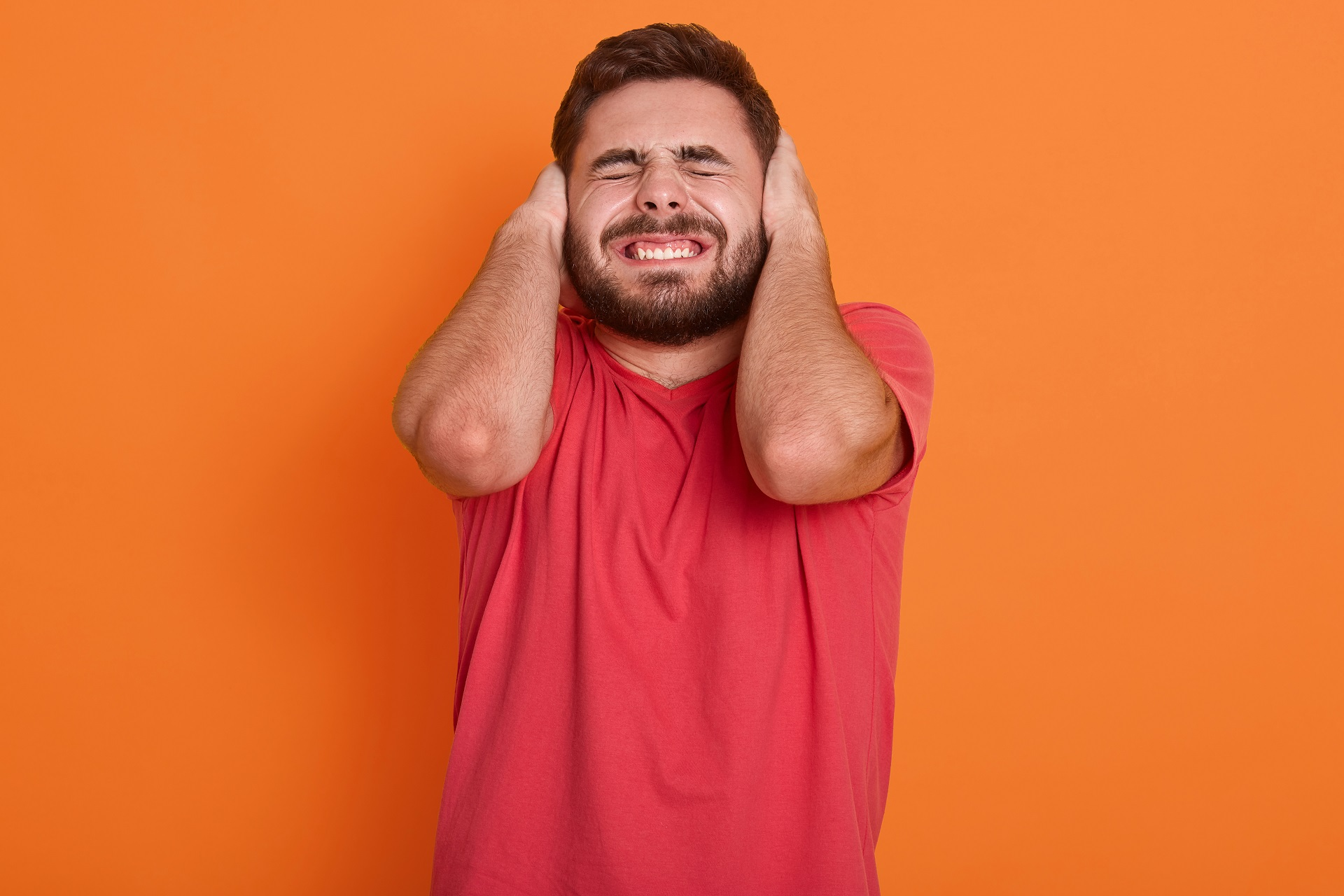 Man covering his ears due to a loud noise