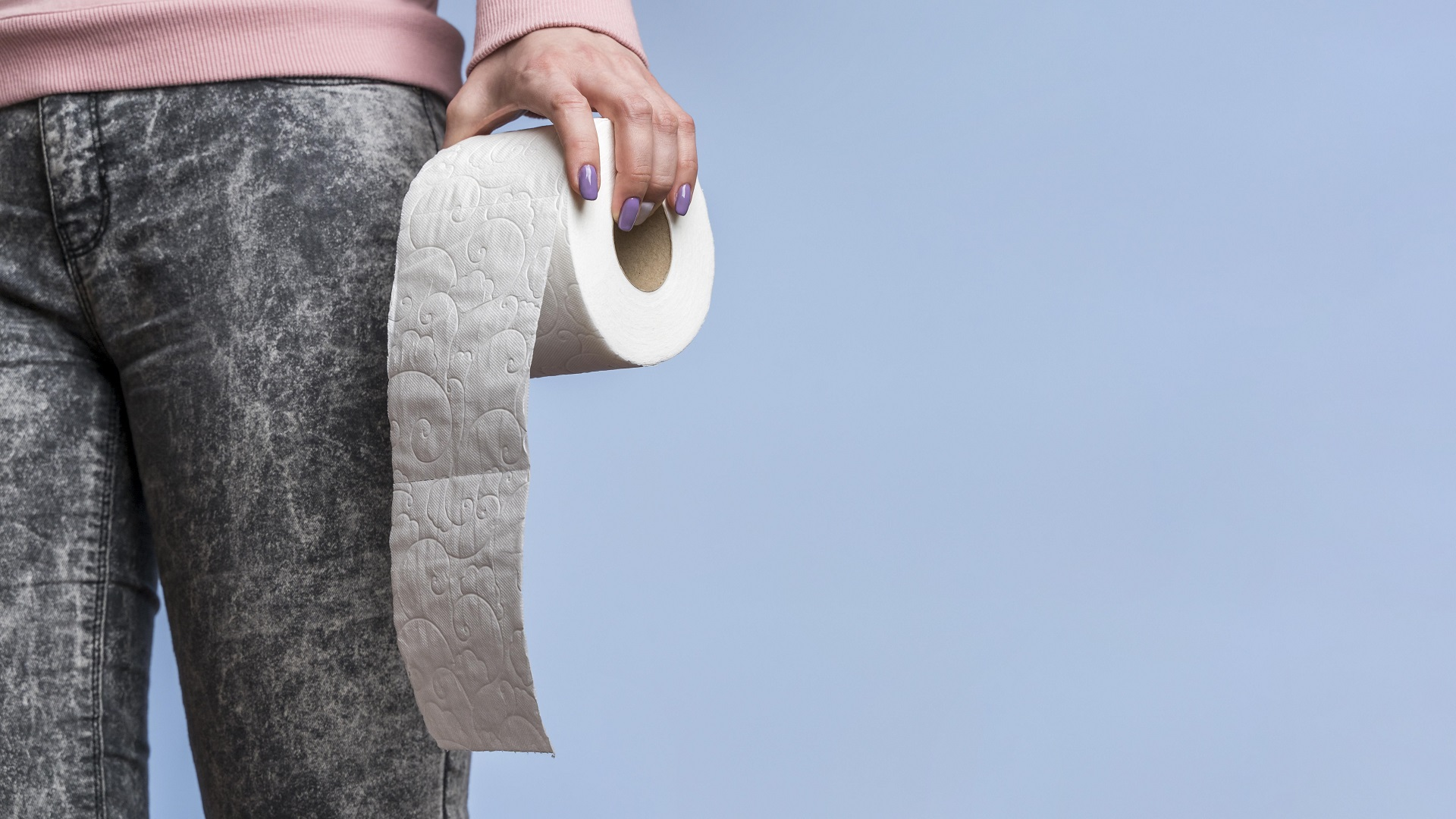 Woman holding a roll of toilet paper