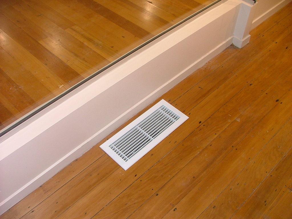 A floor vent in a wooden floor