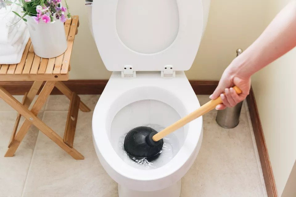 Plunger inside the bowl of a clogged toilet