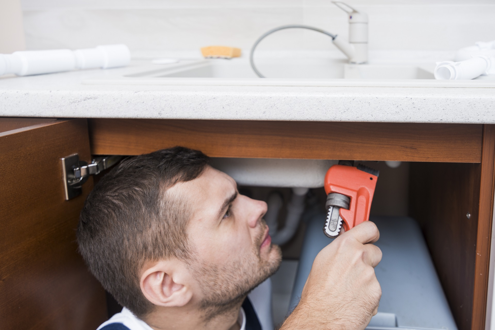 Plumber with a wrench working underneath a kitchen sink in Abbotsford