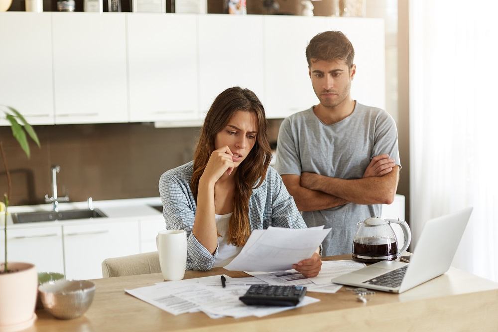 A young couple looking unhappy because of unexpected high energy bills due to a inefficient boiler.