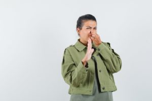 Woman plugging nose due to bad smell coming from the sink drain