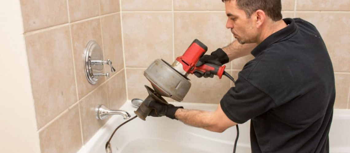 Man using a drain snake on his clogged bathtub sink during a plumbing emergency
