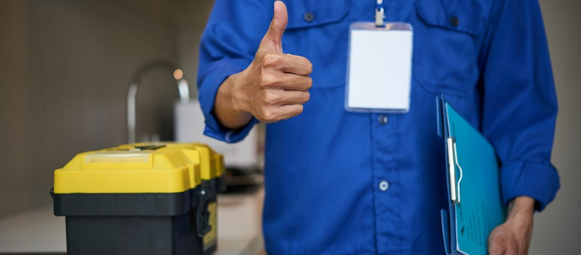 Residential plumber with tool box showing thumbs-up