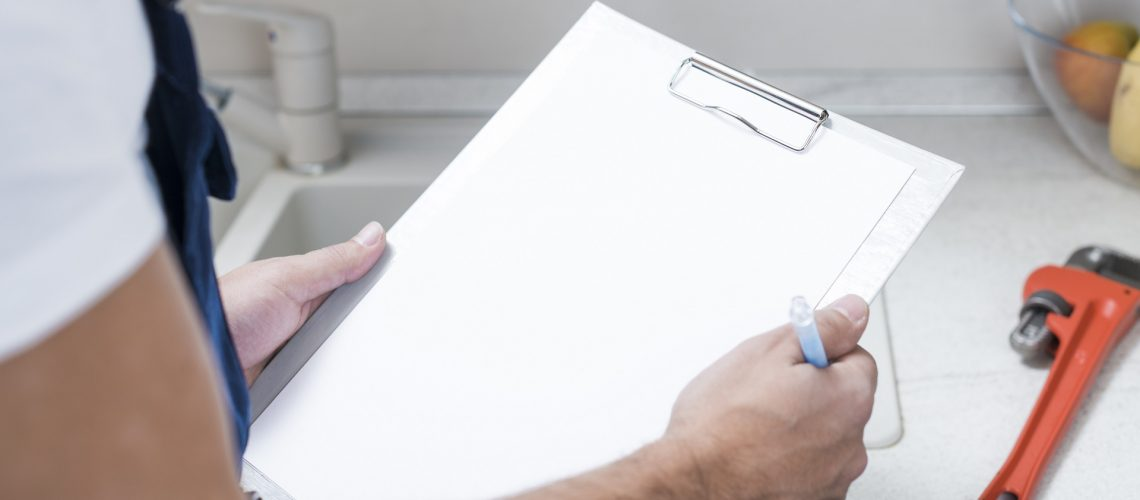 Plumber holding clipboard making list of plumbing issues