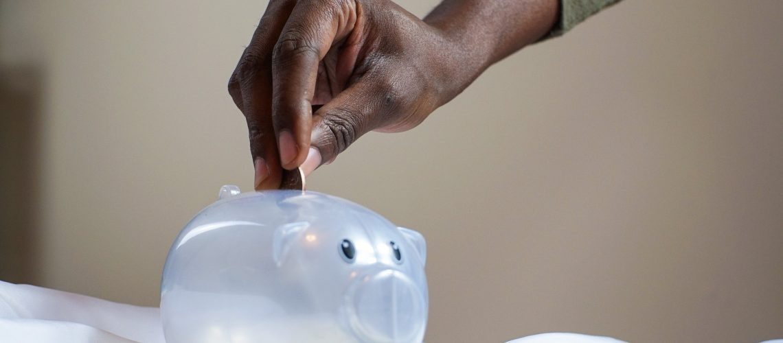Saving money by putting coins into a piggy bank