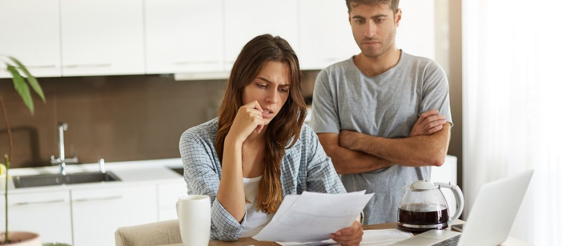 Candid shot of young American man and woman dressed casually feeling stressed while managing finances in kitchen together, calculating expenses, paying utility bills online on laptop computer